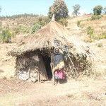 A local village woman stands beside her original home