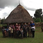 The team gathers in front of one of the local mud huts in Ethiopia