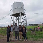 "The team gets to stand in front of the ""Faith"" water well. This is the first water well drilled by Hopethiopia with a production of about 10,000L per hour. The water is a great benefit to the Hopethiopia project site and to the local community."