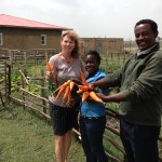 Diane, Sophia, and Hailu show off some of the healthy produce that came from the first garden project that they are standing in front of. The team ate much of the produce and it was very healthy and delicious.