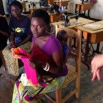 "One of our sponsored women with her child on her back receives a ""Pillow Case"" dress."