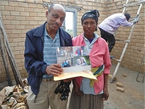 Melaku spends some time with Tirunesh, one of the sponsored women in Ethiopia.  They stand inside one of the new children's homes that has been built using the Hydraform bricks that are built at the Hopethiopia brick building facility.