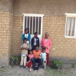 Tirunesh and her children stand in front of their new home
