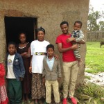 Tirunesh and her children stand in front of their original home